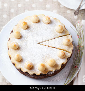 Traditional English Easter cake with marzipan decoration on a white plate Top view - Stock Photo