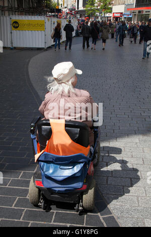 Travelling Senior, Pensioner disabled person using Powered Mobility scooter on the move in Liverpool One, Merseyside, - Stock Photo