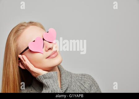 Young woman daydreaming with hearts on her eyes looking up - Stock Photo