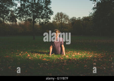 A young woman is siting on the grass in the park in the evening - Stock Photo