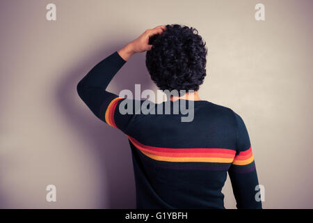A young man is scratching his head in confusion - Stock Photo