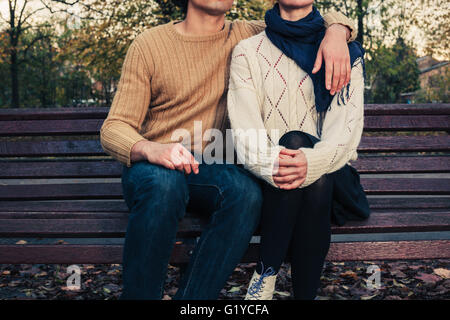 A young couple is sitting and holding each other on a park bench in autumn - Stock Photo