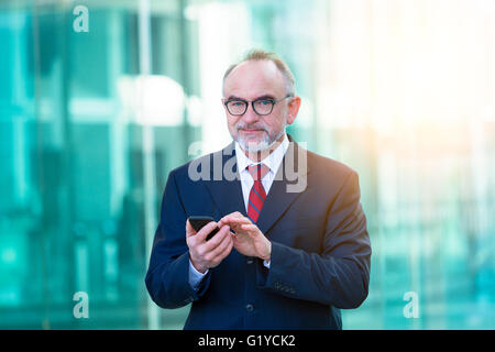 Businessman typing on smartphone - Stock Photo