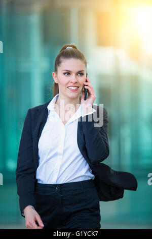 Businessman talking on mobile phone in financial district - Stock Photo
