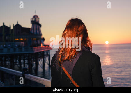 A young woman is walking on the coast at sunset and is admiring the sea - Stock Photo