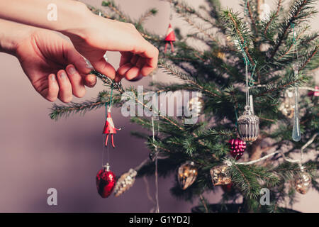Hands decorating a christmas tree with all kinds of colorful things - Stock Photo