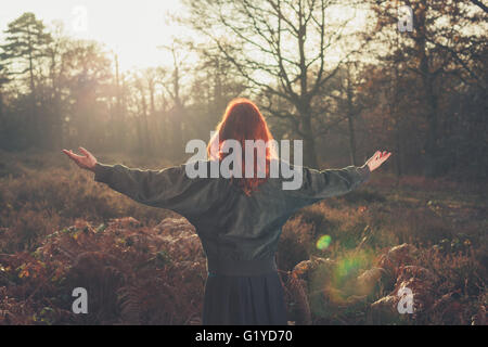A young woman is raising her arms in joy as she is standing in a forest at sunset - Stock Photo