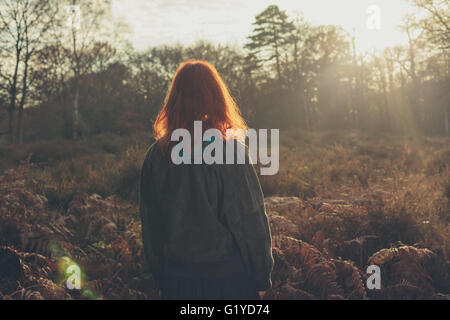 A young woman is standing in a forest at sunset - Stock Photo