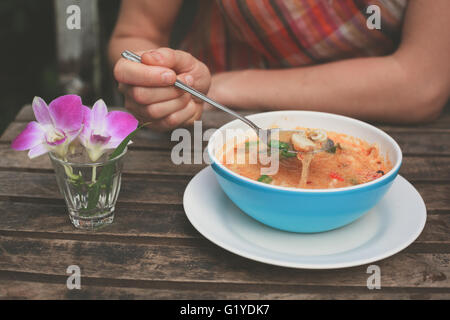 A young woman is eating tom yum soup at a table outside - Stock Photo