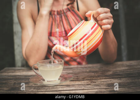 A young woman is sitting at a table and is pouring a cup of tea - Stock Photo