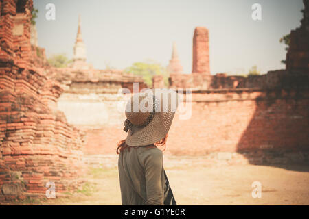 A young woman is exploring the ancient ruins of a buddhist temple city - Stock Photo