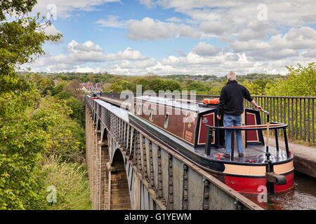 Man with his hand on the tiller, steering narrowboat over the Pontcysyllte Aqueduct, built by Thomas Telford, on - Stock Photo