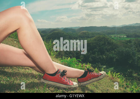 The legs of a young woman as she is relaxing on a hill in the tropics - Stock Photo