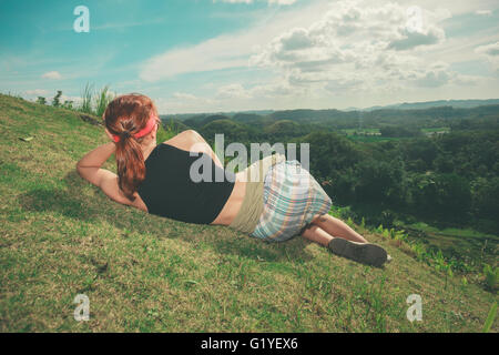 A young woman is lying on the hillside and is admiring the view of the chocolate hills in Bohol, Philippines - Stock Photo