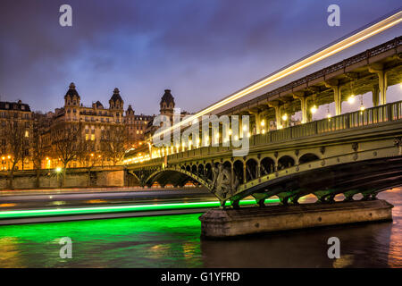 Paris Bir-Hakeim bridge at twilight with clouds and light trails of boats on the Seine River. 16th Arrondissement, - Stock Photo