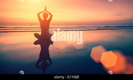 Amazing yoga background, silhouette of woman on the beach at  beautiful sunset, meditation and mindfulness. - Stock Photo