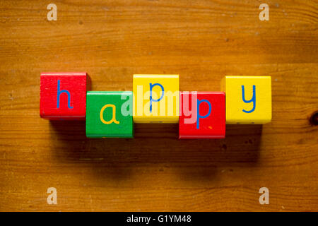 Colorful wooden blocks spelling the word/letters HAPPY - Stock Photo