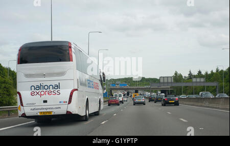National Express bus approaching busy traffic anti clockwise on the M25 London Orbital motorway - Stock Photo