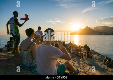 RIO DE JANEIRO - FEBRUARY 26, 2016: Crowds of people gather to watch the sunset on the rocks at Arpoador at Ipanema - Stock Photo