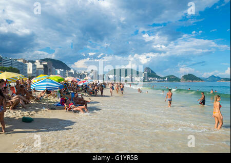 RIO DE JANEIRO - FEBRUARY 27, 2016: A rising tide pushes waves closer to beachgoers enjoying an afternoon on Copacabana - Stock Photo