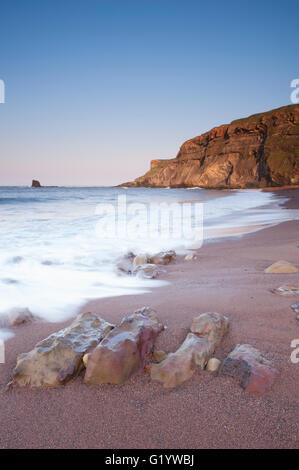 Towering cliffs, Black Nab, calm sea, smooth sand, rocky shoreline, clear blue sky & evening sun - picturesque Saltwick - Stock Photo