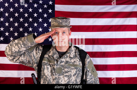 Veteran male soldier, facing forward, saluting with USA flag in background. Soldier armed with military weapon and - Stock Photo