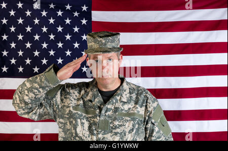 Veteran male soldier, facing forward, saluting with USA flag in background. - Stock Photo