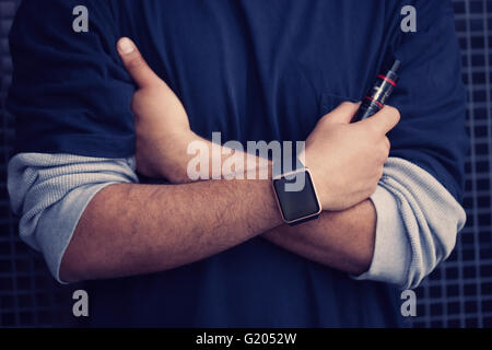 Hands of African model wearing smart wrist watches and holding vaporizer.Modern gadget that lets you always stay - Stock Photo