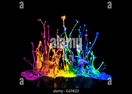 This is a colorful paint splash on a speaker isolated on a black background. - Stock Photo