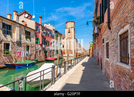 Narrow street and boats on canal between colorful houses under blue sky in Venice, Italy. - Stock Photo
