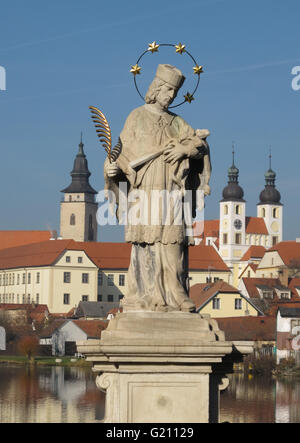 marble statue of St. John holding cross and feather pen with Telc towers in background, Southwestern Moravia, Czech - Stock Photo