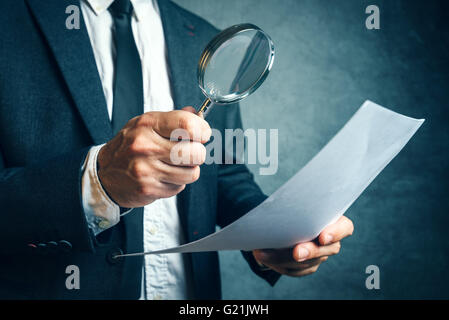 Tax inspector investigating financial documents through magnifying glass, forensic accounting or financial forensics, - Stock Photo
