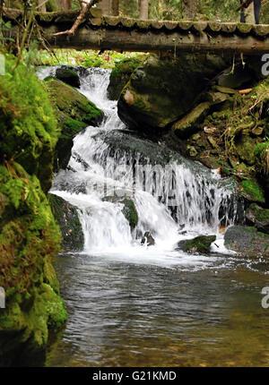 waterfalll with wooden bridge over on Bila Opava river in Jeseniky mountains near Karlova Studanka spa resort - Stock Photo
