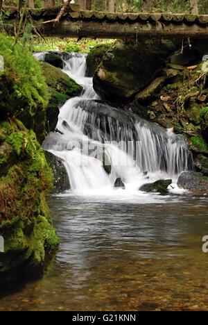 waterfall on Bila Opava river with wooden bridge on hiking trail above in Jeseniky mountains near Karlova Studanka - Stock Photo