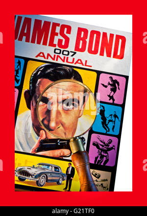 Magnifying glass on detail of 1965  'The James Bond 007 Annual' Sean Connery with Walther PPK gun and Aston Martin - Stock Photo
