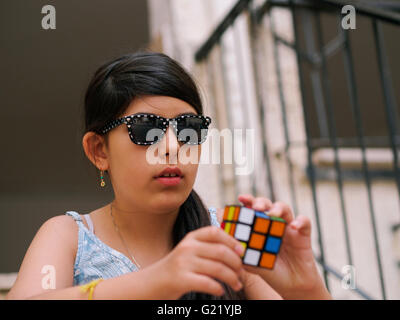 young preteen girl with sunglasses attempts to solve Rubik's Cube - Stock Photo