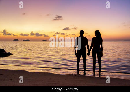 Silhouette young couple standing on the beach holding hands and watching  the tropical sunset - Stock Photo