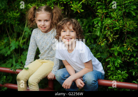 Girl with boy sit on the fence in the park and laughing - Stock Photo
