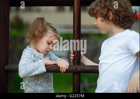 Little girl standing on the playground next to the boy and crying - Stock Photo