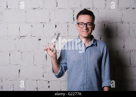 Handsome young male hairdresser in glasses smiling, posing with scissors and comb, on gray brick wall background, - Stock Photo