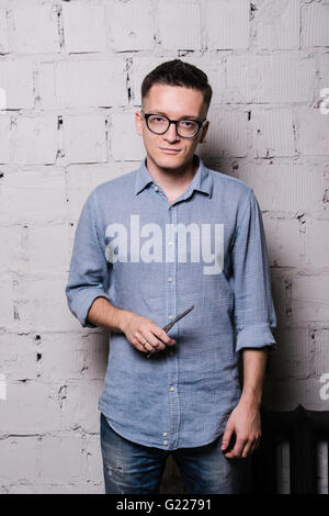 Portrait of young male hairdresser in glasses, posing with scissors, on gray brick wall background, front view - Stock Photo