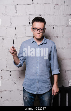Portrait of young male hairdresser in glasses, posing with scissors, on gray brick wall background, front view, - Stock Photo