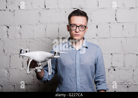 Young stylish Man in glasses holding the quadcopter drone DJI Phantom 4 on a grey brick wall - Stock Photo