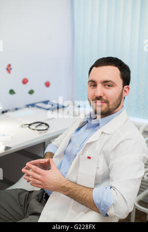 Calm doctor or consultant sitting at desk with his stethoscope on  table looking to the camera - Stock Photo