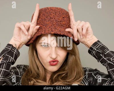 Portrait of A Woman Being or Acting Silly Pulling Faces and Acting the Fool With Finger Gestures and Humorous Facial - Stock Photo
