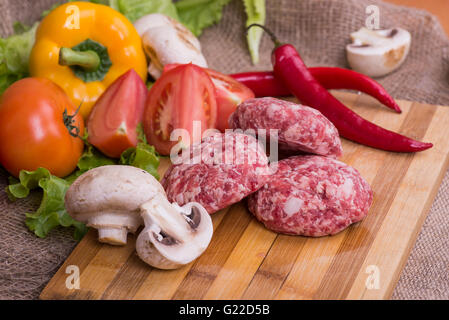 fresh raw cutlet with herbs and tomatoes, mushrooms, pepper - Stock Photo