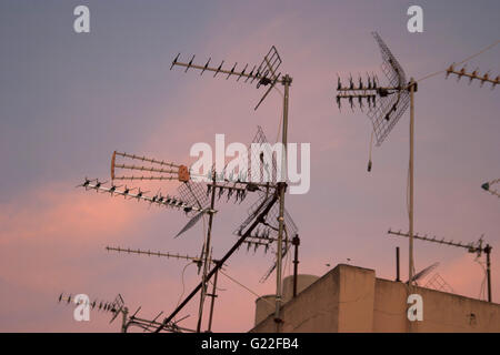 a poetic picture of television aerials on rooftop with cloudy pink and blue sky at sunset, Palma de Mallorca, Spain, - Stock Photo