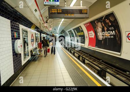 Passengers wait on the platform at Shepherds Bush London underground station for a train to arrive. - Stock Photo
