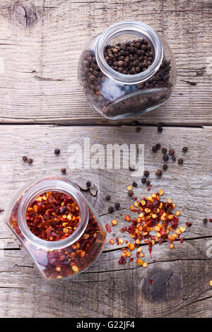 Chili flakes and black pepper in jars on wooden background - Stock Photo