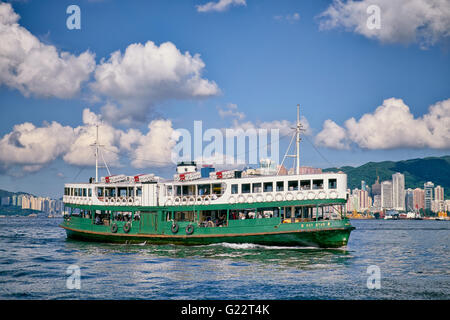HONG KONG, VICTORIA HARBOUR - JUNE 15, 2015: A Star Ferry sets sail to cruise across Victoria Harbour in Hong Kong - Stock Photo
